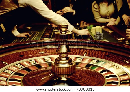 People play casino games: gold spinning roulette with motion of players, croupier (dealer) and roulette in a modern casino. Selected focus used to accent the movement and game activity. - stock photo