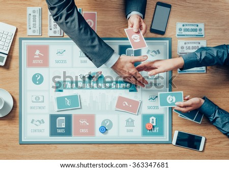People playing a business board game on a wooden table, hands shaking close up, partnership and agreement concept - stock photo