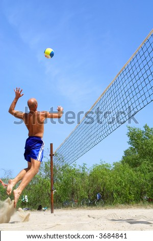 People playing beach volleyball - balding strong man spikes. Shot near Dnieper river, Ukraine.