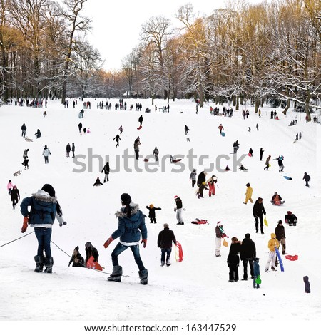 People playing in the winter park. Winter landscape. - stock photo