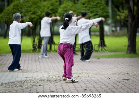 People practising tai chi in the park - stock photo