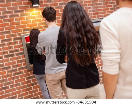 People queuing to withdraw cash at an ATM - stock photo