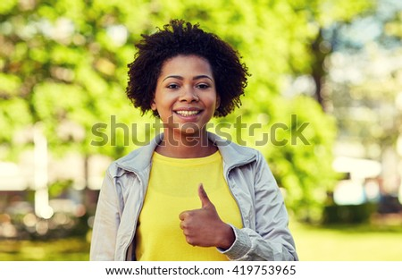 people, race, ethnicity and gesture concept - happy african american young woman showing thumbs up in summer park - stock photo