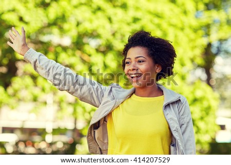 people, race, ethnicity and gesture concept - happy african american young woman waving hand in summer park - stock photo