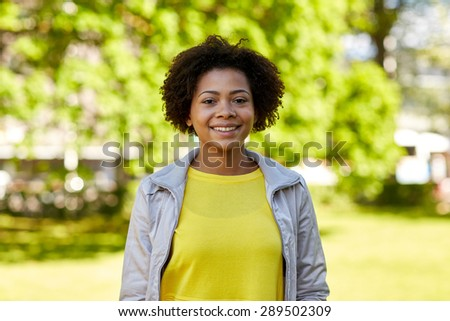people, race, ethnicity and portrait concept - happy african american young woman in summer park