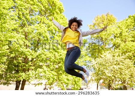 people, race, ethnicity and portrait concept - happy african american young woman in summer park - stock photo