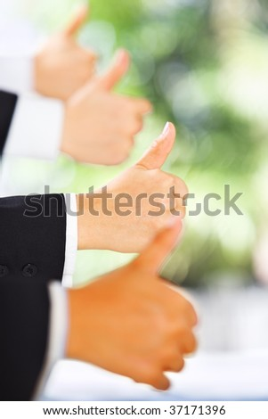 People raise thumbs up in line with green environment background - stock photo