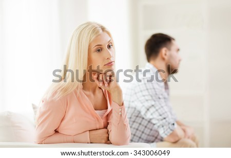 people, relationship difficulties, conflict and family concept - unhappy couple having argument at home - stock photo