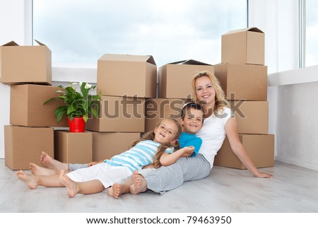 People relaxing in their new home with cardboard boxes and a plant