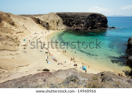 people relaxing, sunbathing and swimming at smaller bay of Papagayo beaches at Lanzarote - stock photo