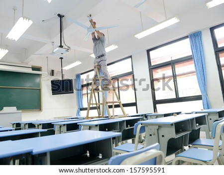 People repairing the fan in a empty classroom.