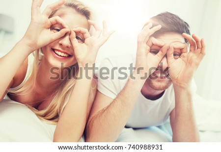 people, rest, love, relationships and fun concept - happy couple lying in bed at home and making finger glasses