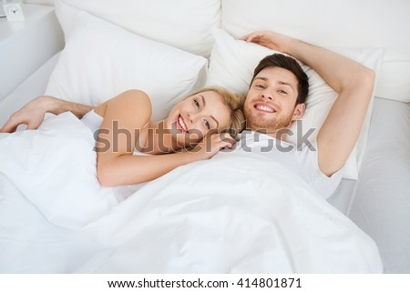 people, rest, love, relationships and happiness concept - happy smiling couple lying in bed at home