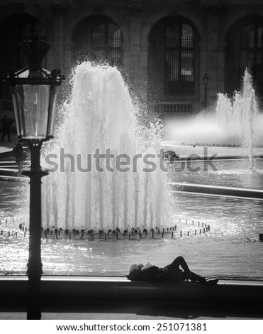 People rest near Louvre museum fountains. Selective focus on the water splashes. Aged photo. Vignette. Black and white. - stock photo