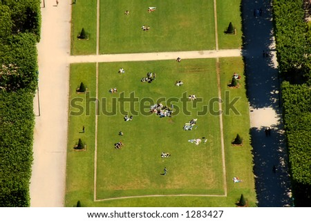 People resting in the park front Eiffel tower. - stock photo