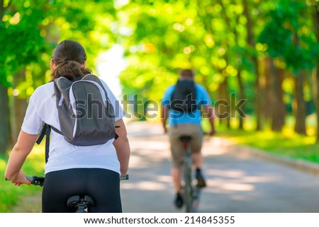 people ride bicycles in summer park - stock photo