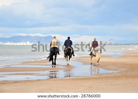people riding on the beach