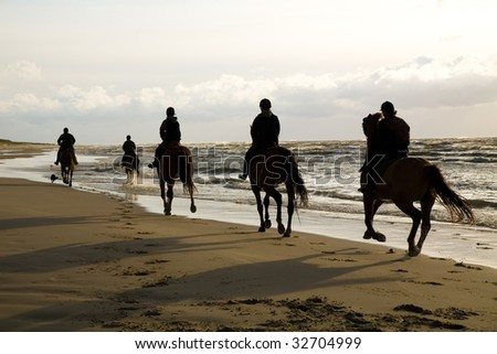 people riding on the beach - stock photo
