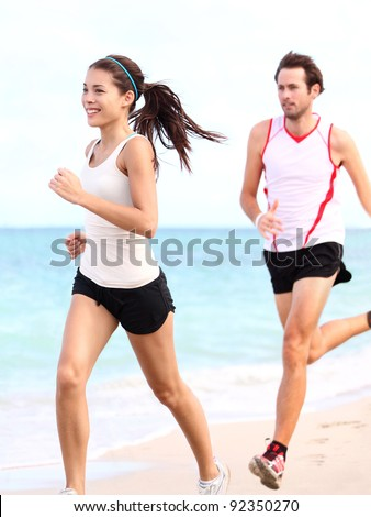 People running: couple runners training outdoors on beach. Young multiracial woman fitness model and caucasian man runner. - stock photo