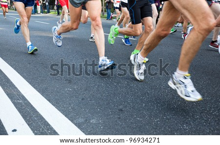 People running fast in a city marathon on street - stock photo