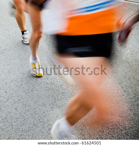People running in city marathon - motion blur - stock photo