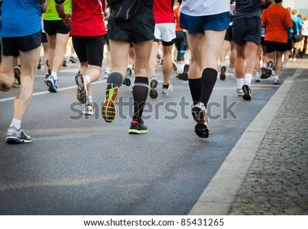 People running in city marathon on a street - stock photo