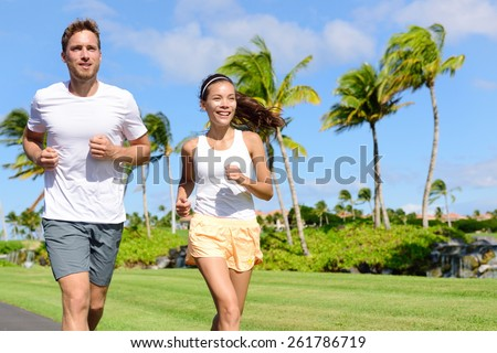 People running in city park. Happy young couple living an active healthy lifestyle jogging training their cardio during summer on road or neighborhood street. Multiracial group, Asian and Caucasian. - stock photo