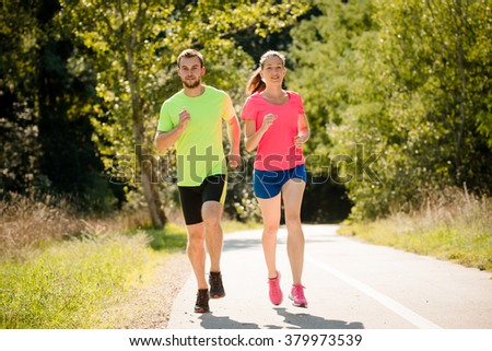 People running together in summer sunny park - stock photo