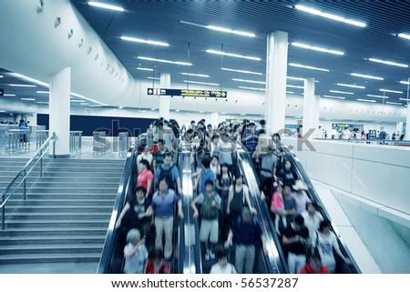 People rush on a escalator motion blurred - stock photo