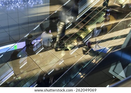 People rushing in the escalator. motion blur - stock photo