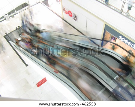 "people rushing on the elevators, ""speed"" is seen on the right side"