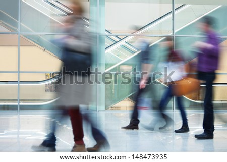 people rushing through corridor - stock photo