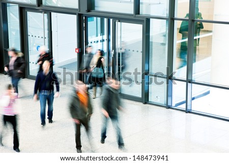 people rushing through corridor - stock photo