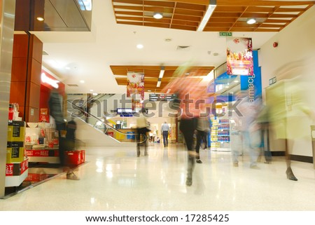 people's motion blur in busy shopping mall - stock photo