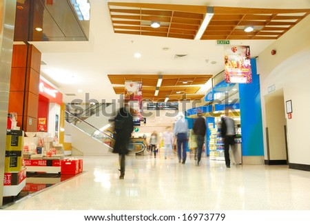 people's motion in busy shopping mall - stock photo