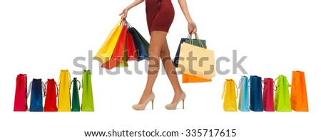 people, sale and consumerism concept - close up of woman in red short skirt and high heeled shoes with shopping bags - stock photo