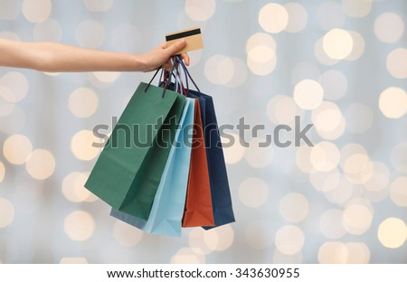 people, sale and consumerism concept - close up of woman with shopping bags and bank or credit card over holidays lights background - stock photo