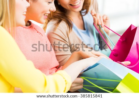 people, sale, consumerism and lifestyle concept - close up of happy teenage girls or young women with shopping bags - stock photo