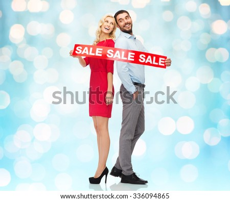 people, sale, discount and holidays concept - happy couple with red sale sign standing back to back over blue holidays lights background - stock photo