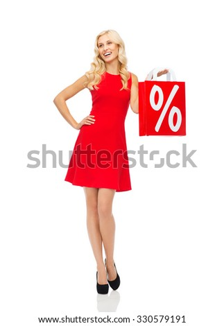 people, sale, discount and holidays concept - smiling woman in red dress holding shopping bag with percent sign - stock photo