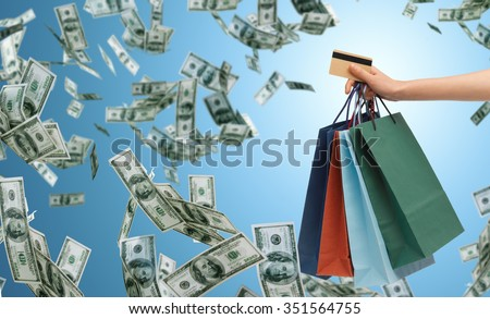 people, sale, finance and consumerism concept - close up of male hand holding shopping bags and bank or credit card over blue background and money rain - stock photo