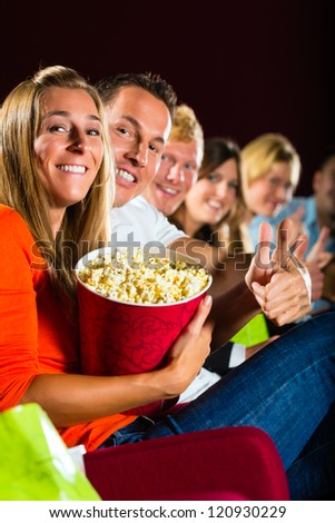 People see a movie in the cinema and have fun they smile at the camera - stock photo