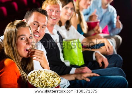 People see a movie in the cinema and have fun they smile at the camera
