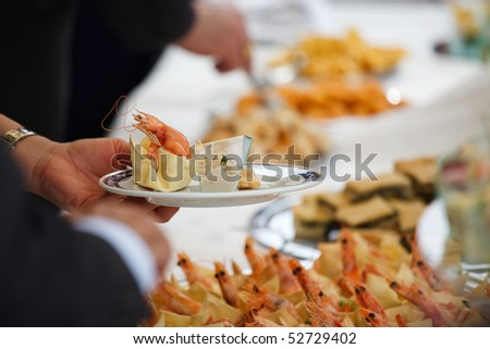 People serving at wedding buffet - stock photo