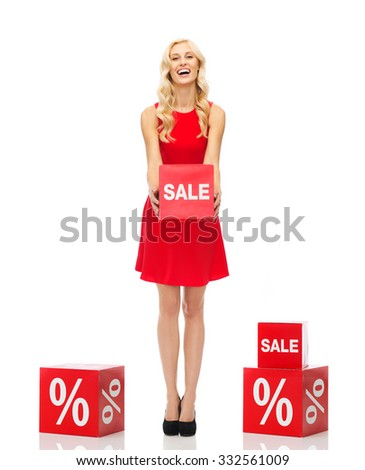 people, shopping, discount and holidays concept - smiling woman in red dress holding cardboard box with sale sign - stock photo