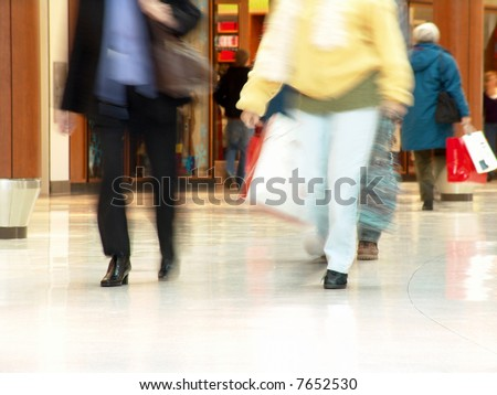 People shopping inside a mall (Blurred motion demonstrates the motion and also protects people privacy) - stock photo