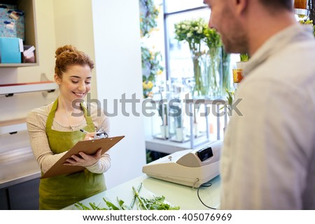 people, shopping, sale, floristry and consumerism concept - happy smiling florist woman with clipboard and man or customer making order at flower shop - stock photo