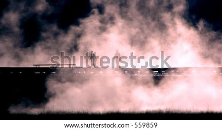 People silhouetted against mist from Grand Prismatic Hot Spring in Yellowstone National Park, Wyoming - stock photo