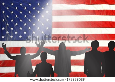 people silhouetted on american flag with spotlight - stock photo