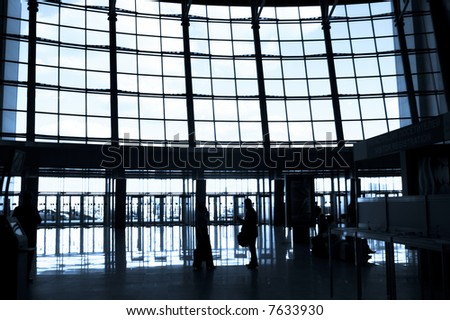 People silhouettes at airport building - stock photo